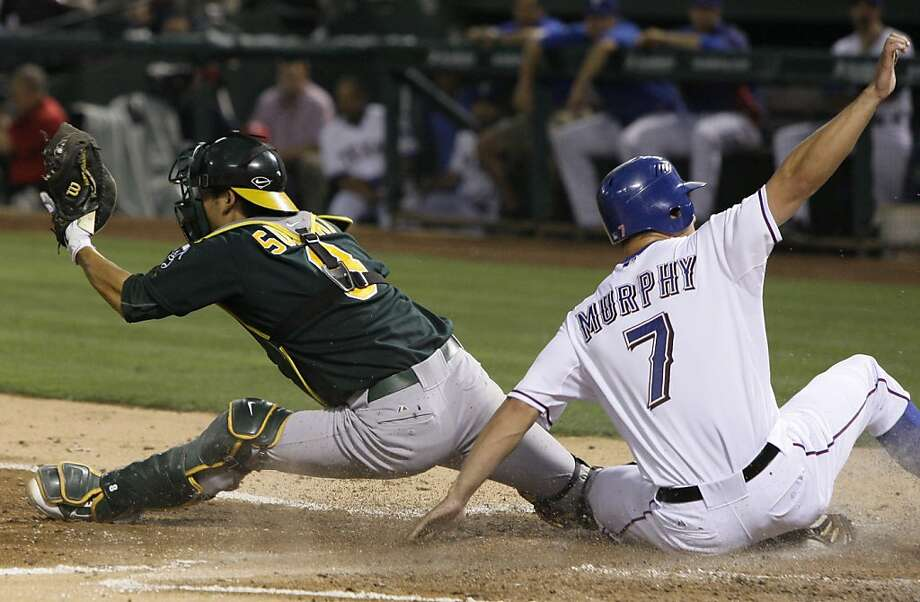 Texas Rangers' David Murphy (7) is forced out at home on a grounder by Julio Borbon as Oakland Athletics catcher Kurt Suzuki is able to keep his leg on the plate in the fourth inning of a baseball game Tuesday, May 10, 2011, in Arlington, Texas. Borbon was safe at first. Photo: Tony Gutierrez, AP