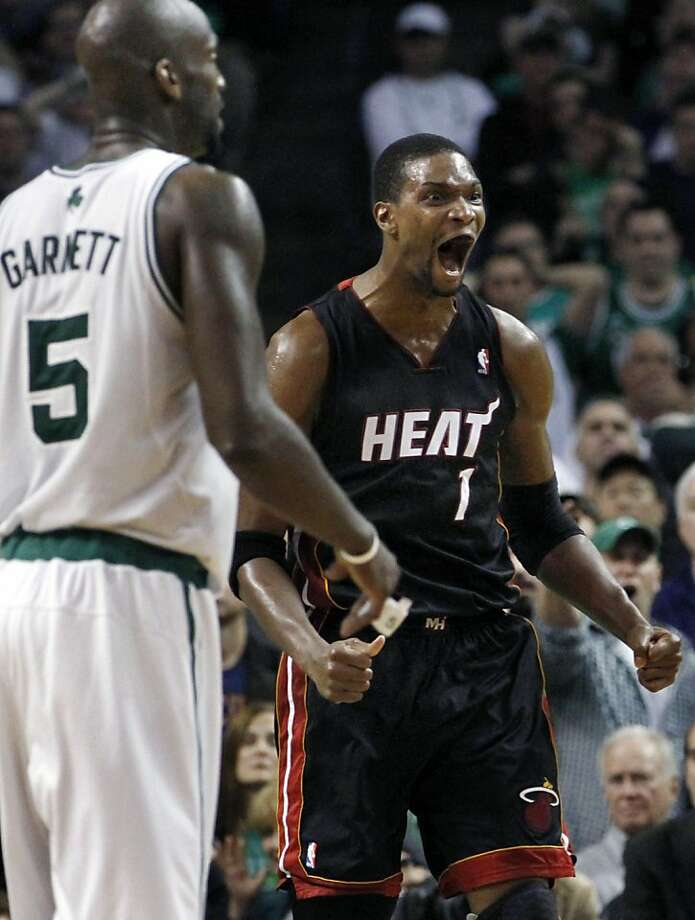 Miami Heat forward Chris Bosh (1) celebrates in front of Boston Celtics forward Kevin Garnett (5) near the end of overtime in Game 4 of a second-round NBA playoff basketball series in Boston on Monday, May 9, 2011. The Heat won 98-90, and lead the series3-1. Photo: Elise Amendola, AP