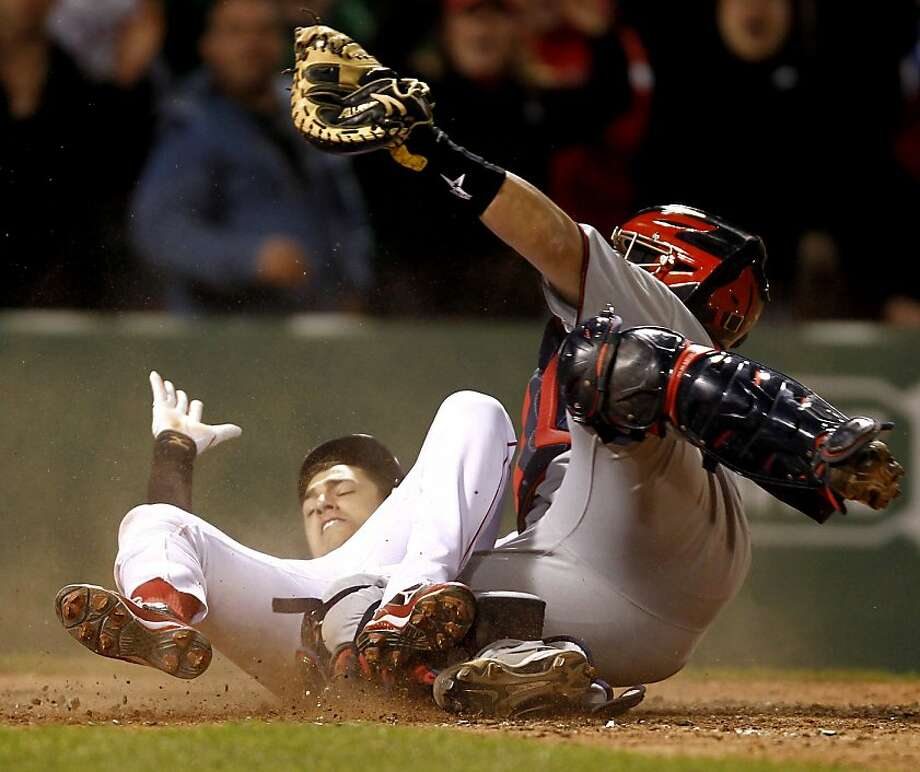 Boston Red Sox's Jose Inglesias slides in safely with the game-winning run as Minnesota Twins catcher Rene Rivera holds up his glove in Boston's 2-1 win in 11 innings in a baseball game at Fenway Park in Boston on Monday, May 9, 2011. Photo: Winslow Townson, AP