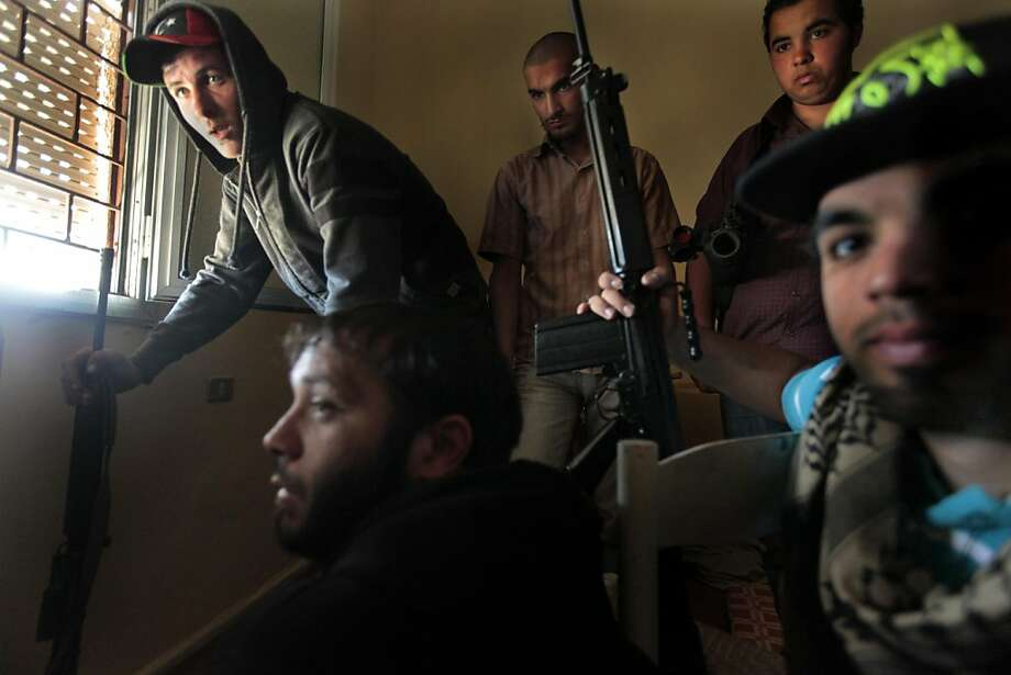 Libyan rebels man a sniper position as they look out through nearly-closed shutters, to avoid being seen, to scope the positions of pro-Gadhafi forces, in Misrata, Libya, Sunday, May 8, 2011. (AP Photo/Ricardo Garcia Vilanova) Photo: Ricardo Garcia Vilanova, AP