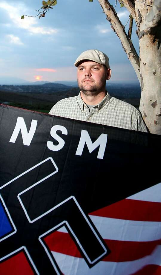 FILE- In  this file photo taken Friday, Oct. 22, 2010, Jeff Hall holds a Neo Nazi flag while standing at Sycamore Highlands Park near his home in Riverside, Calif., Hall, who was running for the Riverside Municipal Water Board and is a Neo Nazi supporter,was fatally shot Monday, May 2, 2011. Photo: Sandy Huffaker, Associated Press