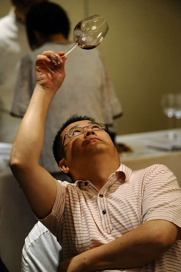 In a picture taken on September 12, 2009 a potential invester samples wine at a wine auction in Hong Kong. Hong Kong investors are turning to rare vintages as an alternative bet for good capital growth, a trend driven by an insatiable demand for imported wine in China. Photo: Antony Dickson, AFP/Getty Images