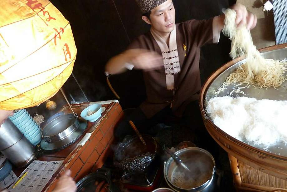 The chef at Tu Hsiao Yueh, the oldest noodle shop in Taiwan (established in 1895), prepares a bowl of Tan Tsai shrimp noodles. The minced pork sauce that goes on top comes from a pot that, legend has it, has been in continuous use for decades. Photo: Spud Hilton, The Chronicle