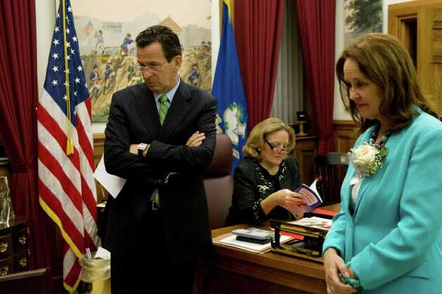 Gov. Dan Malloy and Secretary of the State Denise Merrill watch a news broadcast while Cathy Malloy sits at the governor's desk reading on Feb. 16, 2011. Photo: Kathleen O'Rourke / Stamford Advocate