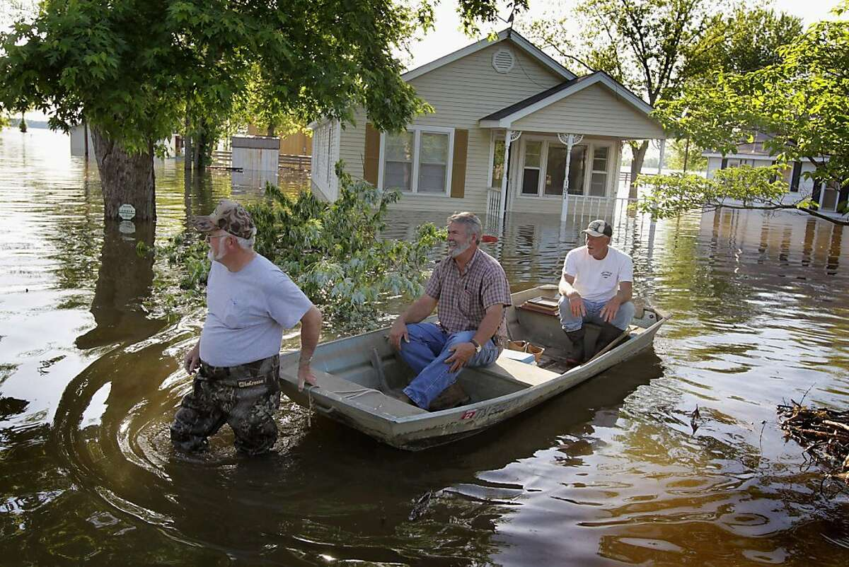 FINLEY, TN - MAY 06: Nathan Moore (L), Steve Richardson (C) and Ronald Moore check on flood damage to their homes in Big Boy Junction May 6, 2011 near Finley, Tennessee. Heavy rains have left the ground saturated, rivers swollen, and have caused widespread flooding in Missouri, Illinois, Kentucky, Tennessee, and Arkansas.