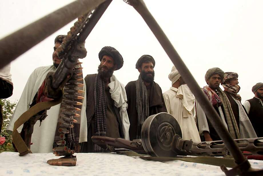 Surrendering Taliban militants stand with their weapons as they are presented to the media in Herat on April 27, 2011. Fifteen Taliban fighters from Afghanistan's Farah province surrendered to government troops in Herat, west of the capital city of Kabul. Photo: Aref Karimi, AFP/Getty Images