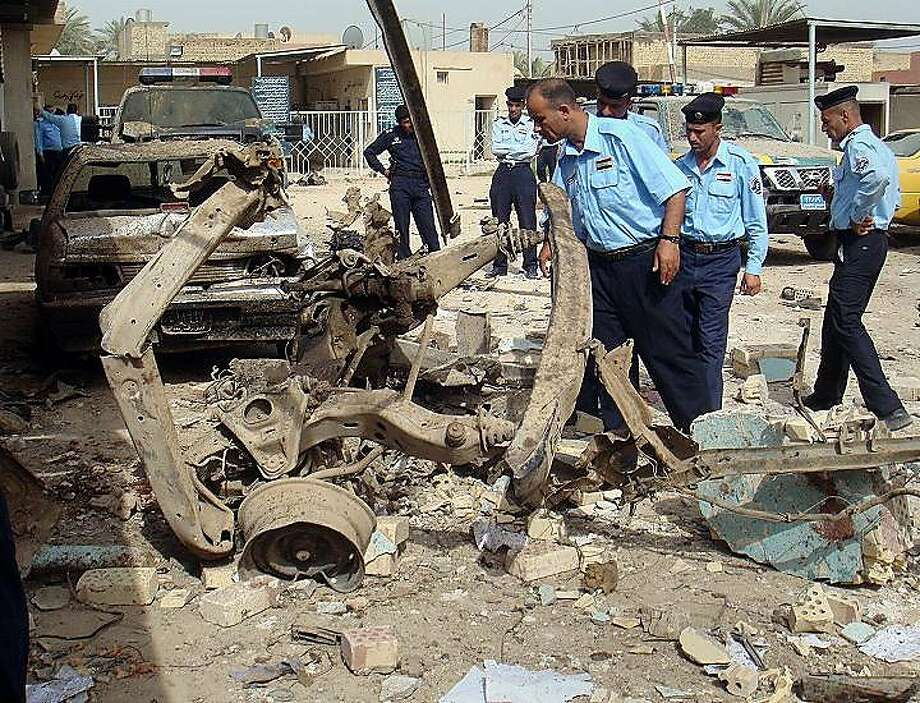 Iraqi security forces inspect the scene of a car bomb attack in Hillah, about 60 miles (95 kilometers) south of Baghdad, Iraq, Thursday, May 5, 2011.  A suicide car bomber crashed his vehicle into a barrier outside a police building in central Iraq on Thursday morning, killing and wounding dozens of policemen, a local councilman said. Photo: Str, AP