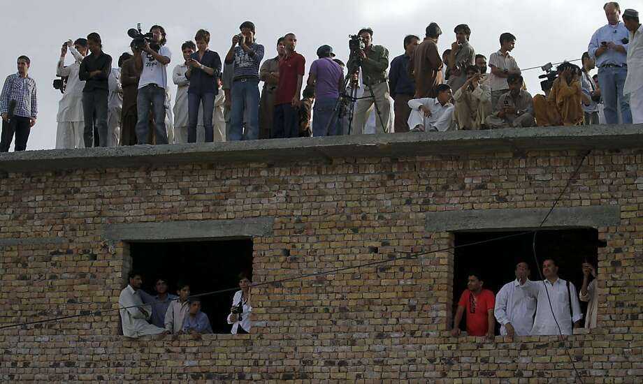 Journalist and local residents gather at a rooftop close to a house where al-Qaida leader Osama bin Laden was caught and killed in Abbottabad, Pakistan on Wednesday, May 4, 2011. The residents of Abbottabad, Pakistan, were still confused and suspicious onWednesday about the killing of Osama bin Laden, which took place in their midst before dawn on Monday. Photo: Anjum Naveed, AP