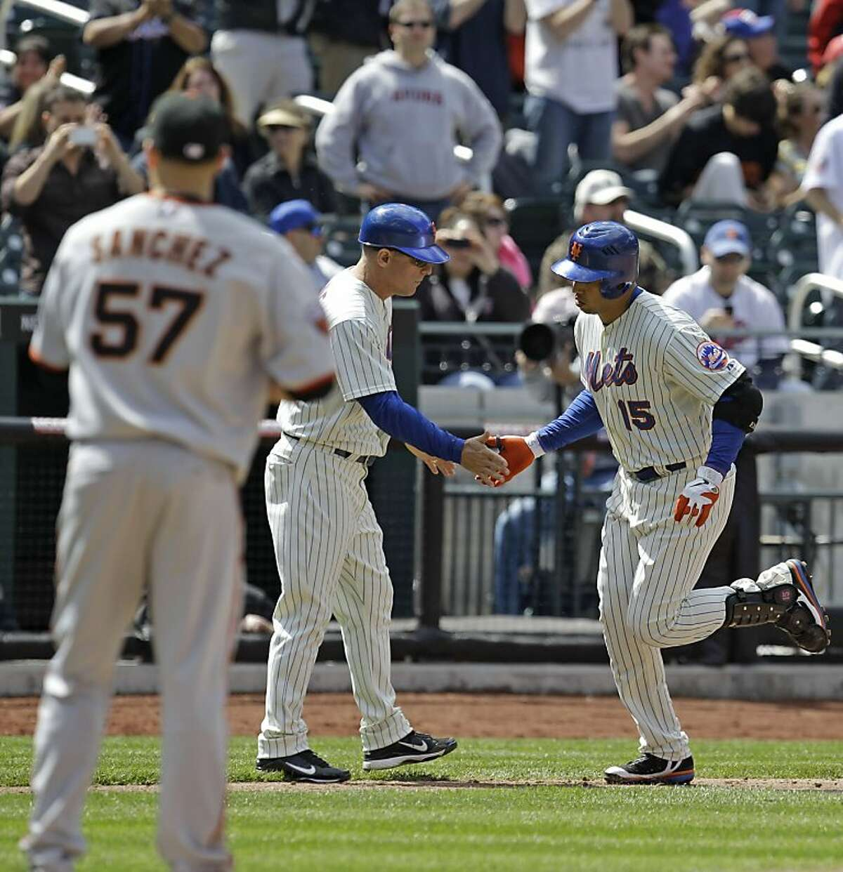 San Francisco Giants starting pitcher Jonathan Sanchez (57) watches as New York Mets third base coach Chip Hale congratulates Carlos Beltran (15) after giving up a fifth-inning, two-run homer to Beltran in their baseball game at Citi Field in New York, Thursday, May 5, 2011.