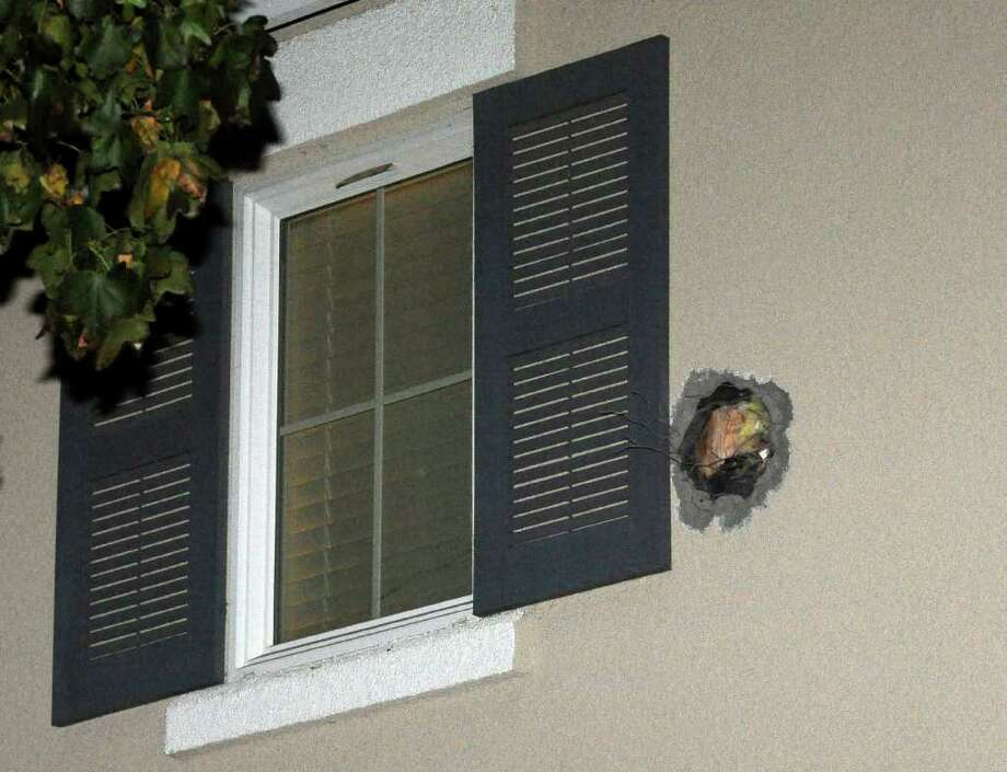 "The exit hole from a misfired cannonball is seen in the second story wall after it traveled through a Dublin, Calif., home on Cassata Place on Tuesday, Dec. 6, 2011. The cannonball misfired during the taping of an episode of the Discovery Channel show ""MythBusters."" The cannonball, fired at the Alameda County Bomb Disposal Range in Dublin, also damaged minivan parked a few blocks away on Springvale Drive. There were no injuries. Sheriff's spokesman J.D. Nelson told the Contra Costa Times that no one was injured and the home's residents didn't even wake up until the dust was settled _ literally on top of them. (AP Photo/Doug Duran, Bay Area News Group) Photo: Doug Duran"
