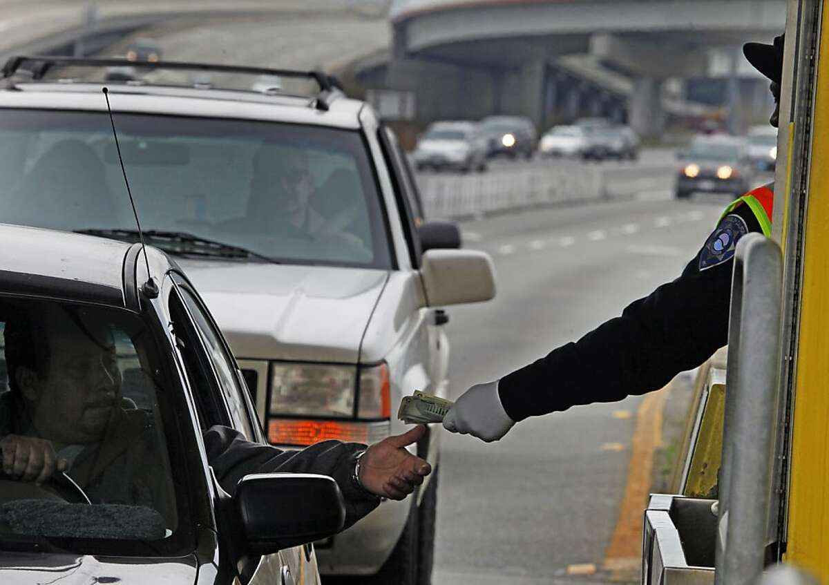 A toll collector reaches for a commuter six dollars payment before heading up to the upper deck of the Bay Bridge. Tuesday Jan 11, 2011.