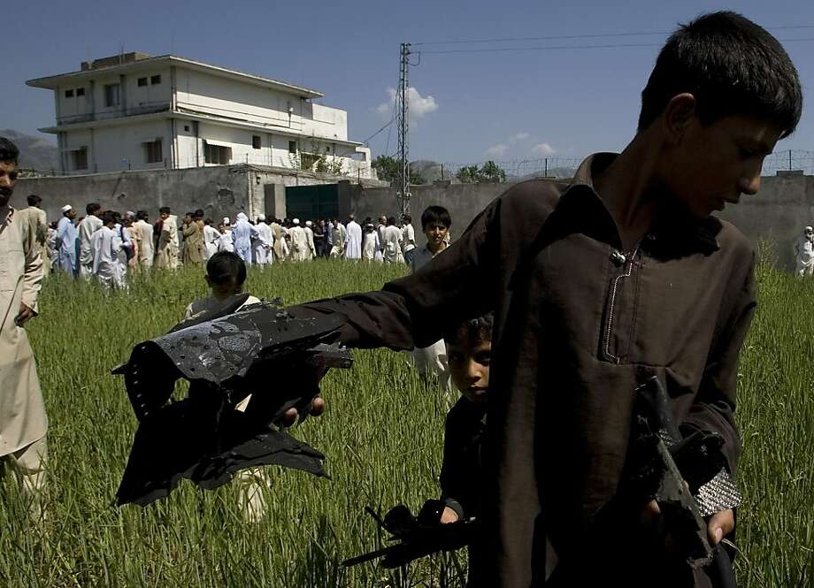 A Pakistani youngster shows metal pieces collected from wheat field outside a house, seen background, where al-Qaida leader Osama bin Laden lived in Abbottabad, Pakistan, on Tuesday, May 3, 2011.  Local residents showed off small parts of what appeared tobe a U.S. helicopter that Washington said malfunctioned and was disabled by the American commando strike team as they retreated, while Pakistan's leader on Tuesday denied suggestions that his country's security forces had sheltered Osama bin Laden. Photo: Anjum Naveed, AP