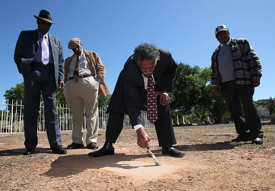 In this photo taken April 26, 2011, Dr. Ralph White,President of the Stockton Black Leadership Council, center, dusts off one of the 36 grave markers that had been moved from the gold rush era Negro Hill Cemetery to the Mormon Island Relocation Cemeterynear Folsom, Calif. The burial plots from Negro Hill went unmarked for more than half a century _ until a contractor hired by the Army Corps of Engineers moved the bodies to make way for a lake, and marked the graves with stones that used a derogatory term for African-American. Now, some 60 years later, a handful of activists are trying to change the offensive gravestones, only to find their good intentions snagged on government bureaucracy. Photo: Rich Pedroncelli, AP