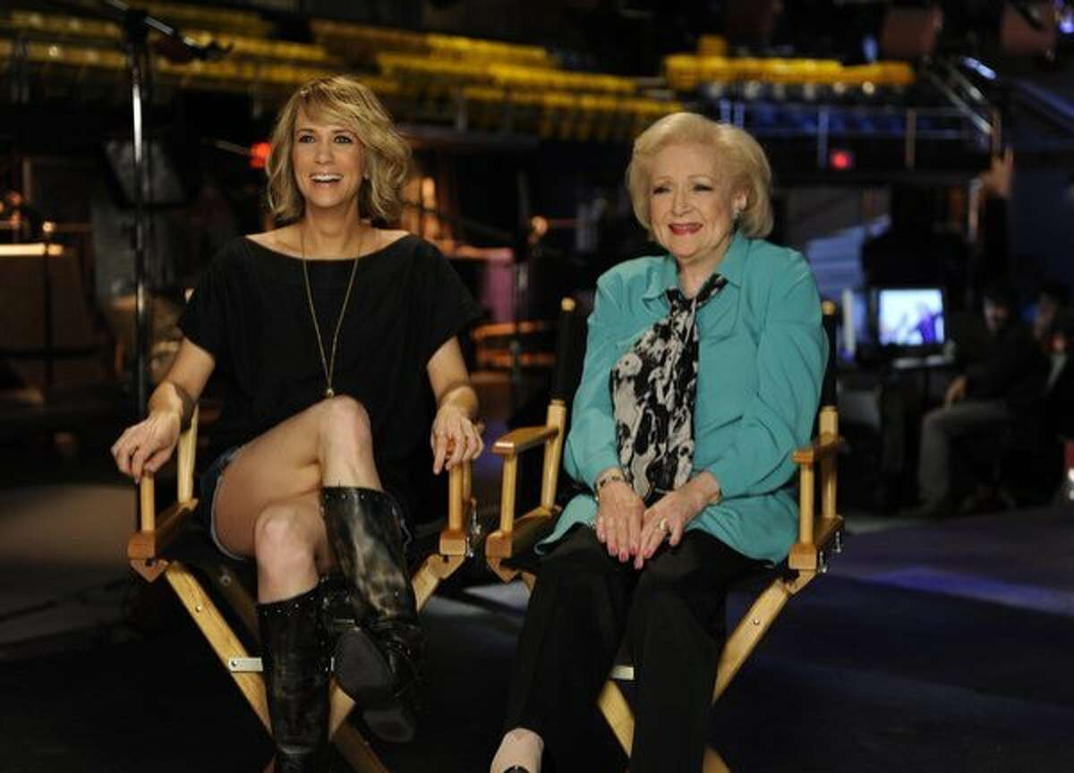 In this publicity image released by NBC, cast member Kristen Wiig,left, and Betty White are shown on the set of
