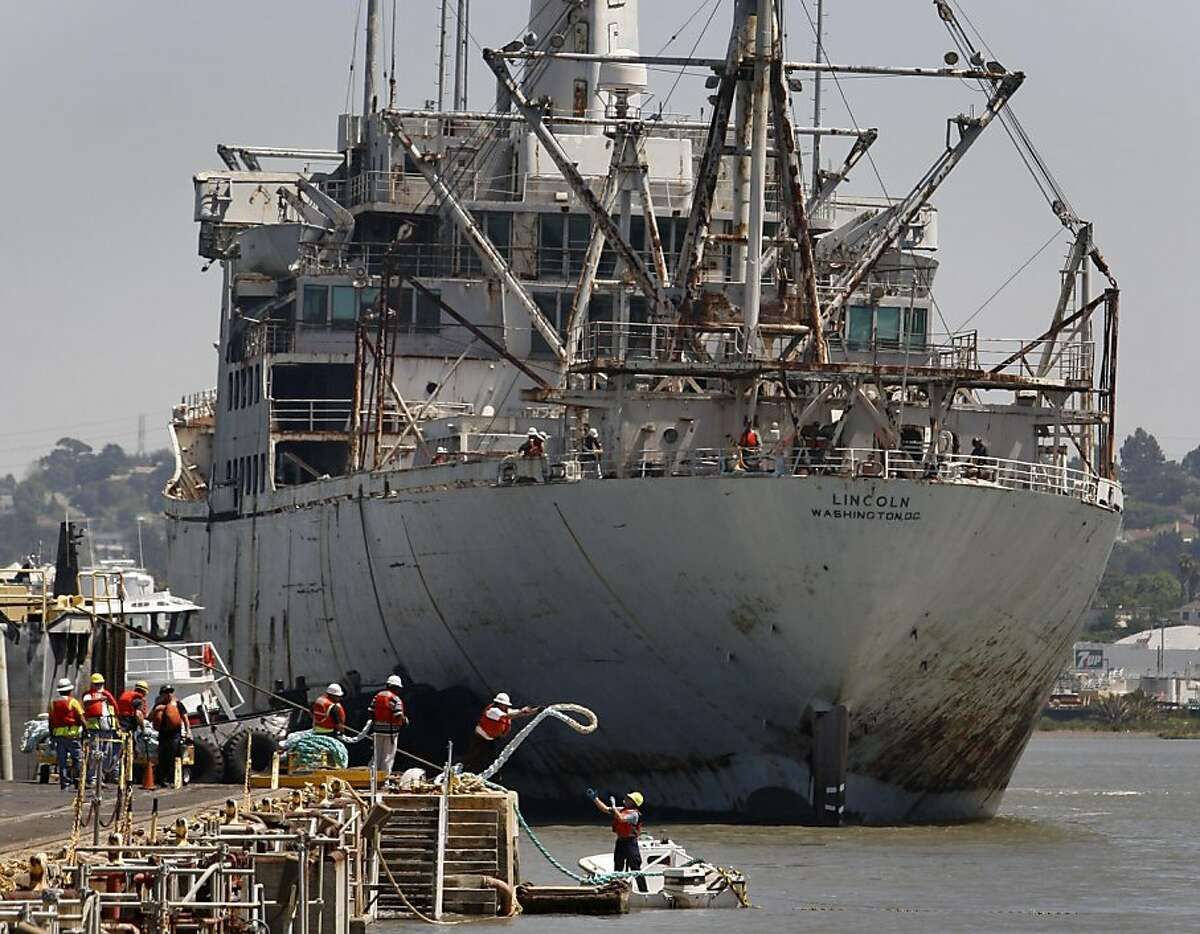 Dock workers prepare to receive the SS Lincoln as it arrives at the Mare Island shipyard in Vallejo, Calif. on Thursday, May 5, 2011, after it was towed from a dry dock facility in San Francisco.