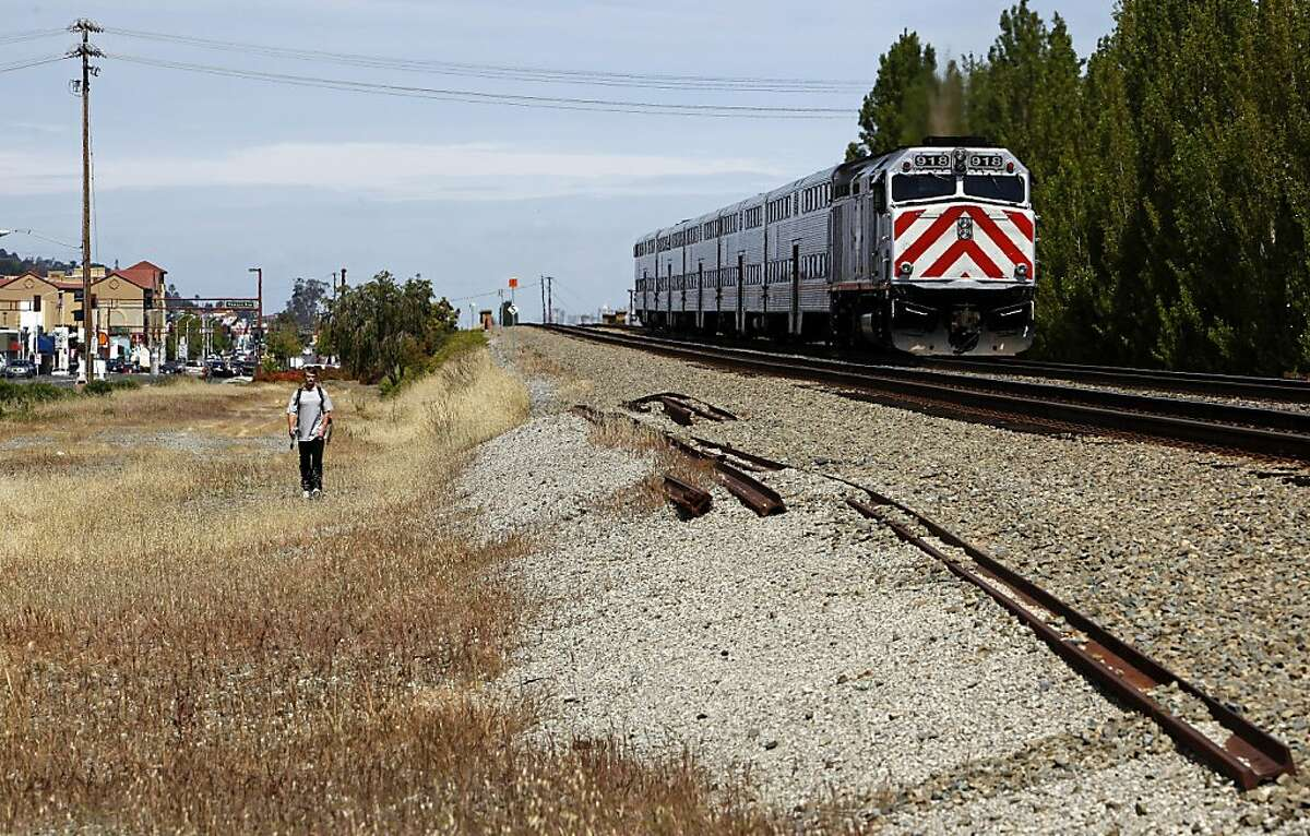 A CalTrain glides along an elevated section of track through San Carlos, Calif. on Wednesday April 29, 2009, as a battle is shaping up on the Peninsula over high-speed rail service through the Peninsula with residents and cities favoring a system that runs through a tunnel or along a sunken trench.