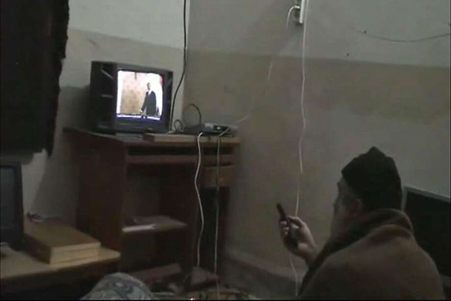 In this undated image from video seized from the walled compound of al-Qaida leader Osama bin Laden in Abbottabad, Pakistan, and released Saturday, May 7, 2011 by the U.S. Department of Defense a man, who the American government identified as Osama bin Laden, watches television, showing an image of U.S. President Barack Obama. U.S. intelligence would not confirm Saturday that the video of bin Laden in the makeshift office was filmed at the Pakistani compound, but they have said they believe he has been holed up in the compound for as long as six years. This and other videos released Saturday show him watching television and rehearsing for terrorist videos. Photo: Department Of Defense, Associated Press