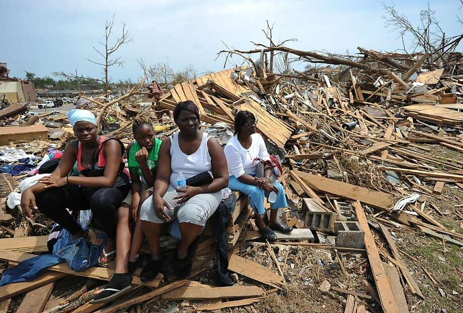 TOPSHOTS Laurie Lee (2nd R) and her family sit at the site of her tornado wrecked home in the Alberta City neighbourhood of Tuscaloosa, Alabama May 1, 2011.  Grieving storm survivors turned to prayer and the good grace of volunteers Sunday across the US south as shattered communities looked to rebuild after the second-worst tornado disaster on record.    TOPSHOTS / Photo: Mandel Ngan, AFP/Getty Images