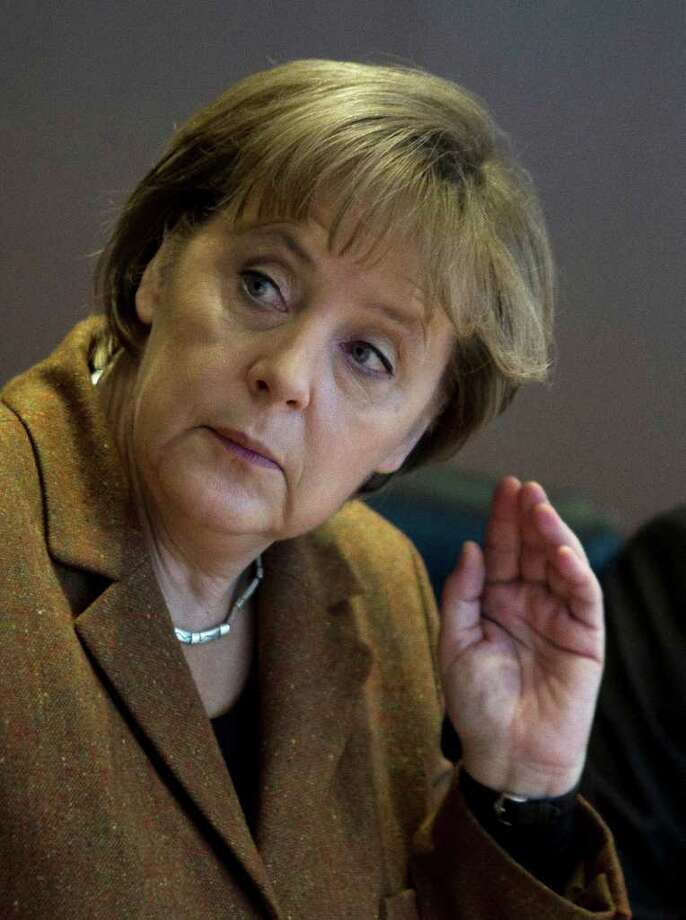 German Chancellor Angela Merkel reacts as she arrives at the weekly cabinet meeting  at the chancellery in Berlin, Wednesday, Dec. 7, 2011.  (AP Photo/Markus Schreiber) Photo: Markus Schreiber / AP