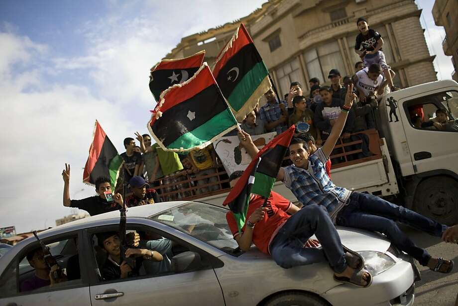 Young Libyan protesters wave pre-Gadhafi national flags and shoot into the air, from car at left, during a rally against Libyan leader Muammar Gaddafi in Benghazi, Libya, Thursday, May 5, 2011. Photo: Bernat Armangue, AP