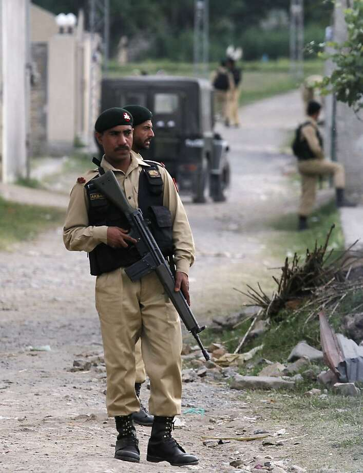 Pakistani army troops guard the perimeter of the walled compound of a house where al-Qaida leader Osama bin Laden was caught and killed in Abbottabad, Pakistan, on Thursday,  May 5, 2011. The residents of Abbottabad, Pakistan, seem to be confused and suspicious about the killing of Osama bin Laden by a U.S. military force, which took place in their midst before dawn on Monday. (AP Photo/Anjum Naveed) Photo: Anjum Naveed, AP