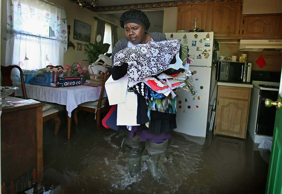 TIPTONVILLE, TN - MAY 04:  Sally Nance walks through floodwater as she helps her neighbors remove clothes from their home home May 4, 2011 in Tiptonville, Tennessee. Heavy rains have left the ground saturated, rivers swollen, and has caused widespread flooding in Missouri, Tennessee, Illinois, Kentucky and Arkansas. Photo: Scott Olson, Getty Images