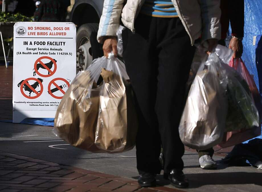 Customers carry bags filled with live birds purchased from the Raymond Young poultry stand at the Heart of the City Farmers' Market in San Francisco, Calif. on Wednesday, May 4, 2011. Signs are posted announcing that sales of live animals will cease at the end of the month. Photo: Paul Chinn, The Chronicle