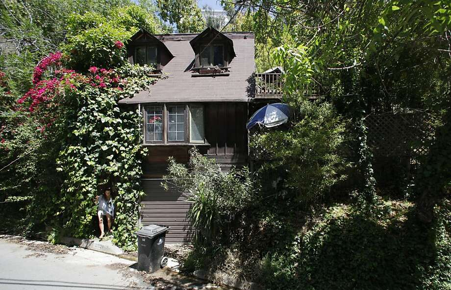 A reporter comes out of the vines covering the small front door of the home of Former Playboy playmate and B-movie actress Yvette Vickers in Beverly Hills, Calif. Tuesday, May 3, 2011. Neighbors learned a badly decomposing body had been inside the home for several months to a year. Photo: Damian Dovarganes, AP