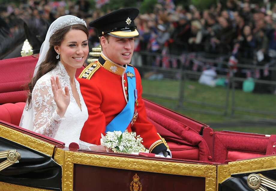 Britain's Prince William and wife Kate, Duchess of Cambridge wave as they travel in the 1902 State Landau carriage along the Processional Route to Buckingham Palace, in London on April 29, 2011. Photo: Dimitar Dilkoff, AFP/Getty Images