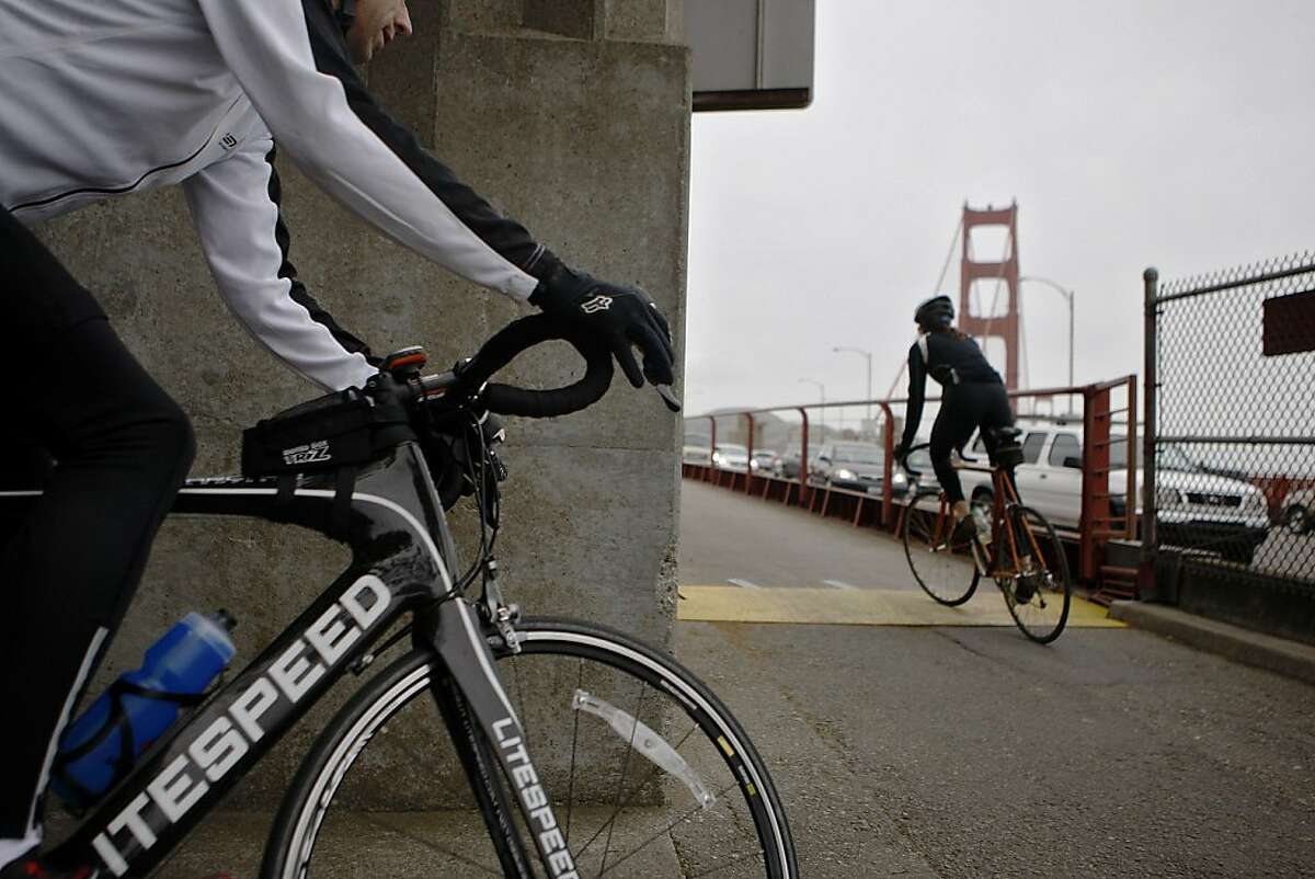 Two bicyclists pedal onto the West side of the Golden Gate Bridge on Friday, April 22, 2011. The west side is bicycles-only after 3:30 pm on weekdays. The Golden Gate Bridge conducted a safety study that recommends restrictions on bicycling across the bridge, most notably a 10 mph speed limits.