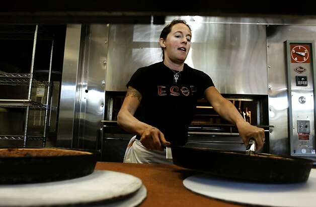 Traci Joyce cooks pizza at Zachary's Chicago Pizza in San Ramon, Ca., on Thursday April 28, 2011. Joyce is one of 8,500 former California Culinary Academy students who is eligible for a rebate from a law suit settlement. Former students alleged the the San Francisco cooking school made bad promises about potential job placement after graduation. Joyce incurred $130,000 in student debt. Photo: Michael Macor, The Chronicle