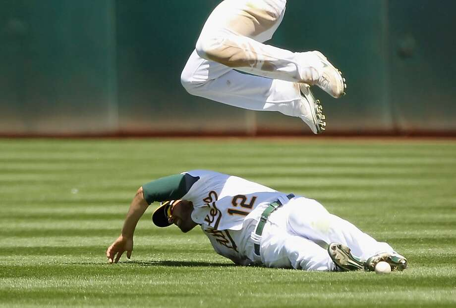 OAKLAND, CA - APRIL 30:  Conor Jackson #28 leaps over David DeJesus #12 of the Oakland Athletics as DeJesus dives for a ball during their game against the Texas Rangers at Oakland-Alameda County Coliseum on April 30, 2011 in Oakland, California. Photo: Ezra Shaw, Getty Images