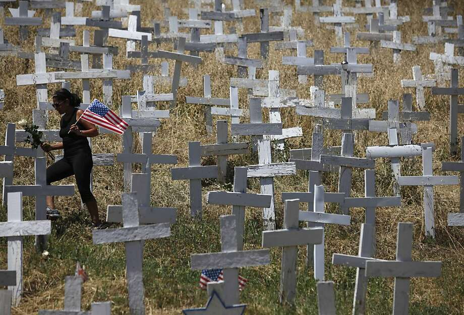 """The day after it was announced that Osama Bin Laden had been killed in Pakistan, Gilly Malmquist of Lafayette places flowers and American flags on a selection of crosses on a hillside in Lafayette that represent 6,038 soldiers who've died in war since 9/11 on Monday Mayl 2, 2011 in San Lafayette, Calif. """"Its time to have closure. I'm hear to start a new day,"""" said Malmquist. Photo: Mike Kepka, The Chronicle"""
