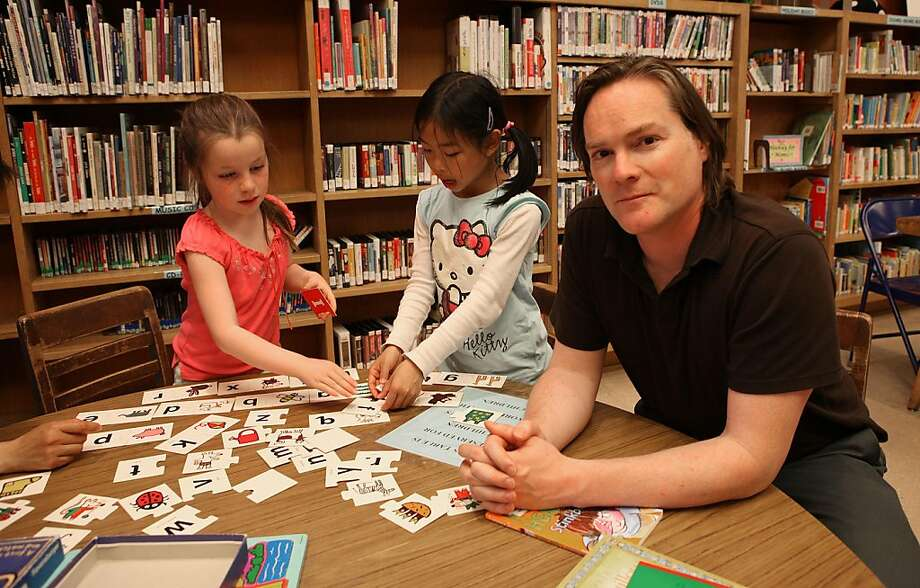 Bob McMillan (right) at the North beach library in San Francisco, Calif., as his daughter Gigi McMillan (left), 7 years old, plays with her friend Cheyanne Chow (middle), 7 years old, after school on Wednesday,  May 4, 2011.  Neighbors who are supporting the new library are battling against unfair influence by the powerful neighborhood group, the Telegraph Hill Dwellers. Photo: Liz Hafalia, The Chronicle
