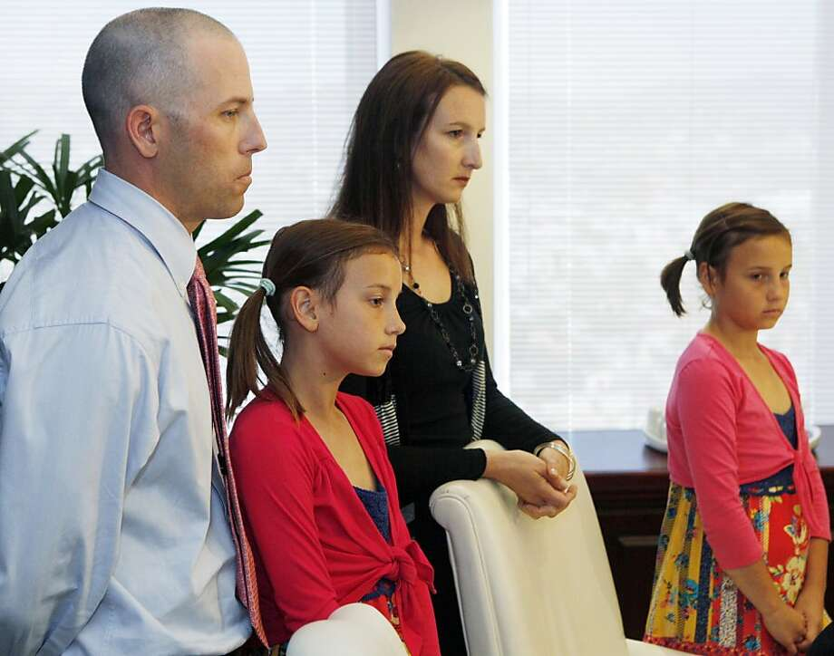 Justin Quinn, left, with wife, Jessica, and their twin daughters: Kylynn, middle, and Taylor, right, take questions from the media during a news conference organized by Los Angeles attorney Gloria Allred in Los Angeles, Wednesday, April 27, 2011. Justin Quinn claims Atlanta Bravespitching coach Roger McDowell made homophobic comments and crude sexual gestures toward fans and threatened him with a bat before the Braves played the San Francisco Giants on April 23, at AT&T Park in San Francisco. Photo: Damian Dovarganes, AP