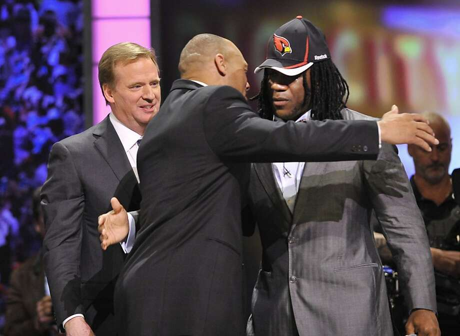 Virginia Tech running back Ryan Williams, right, hugs former defensive back Aeneas Williams as NFL Commissioner Roger Goodell, left, looks on after he was selected by the Arizona Cardinals in the second round of the NFL football draft at Radio City MusicHall ,Friday, April 29, 2011, in New York. Photo: Stephen Chernin, AP