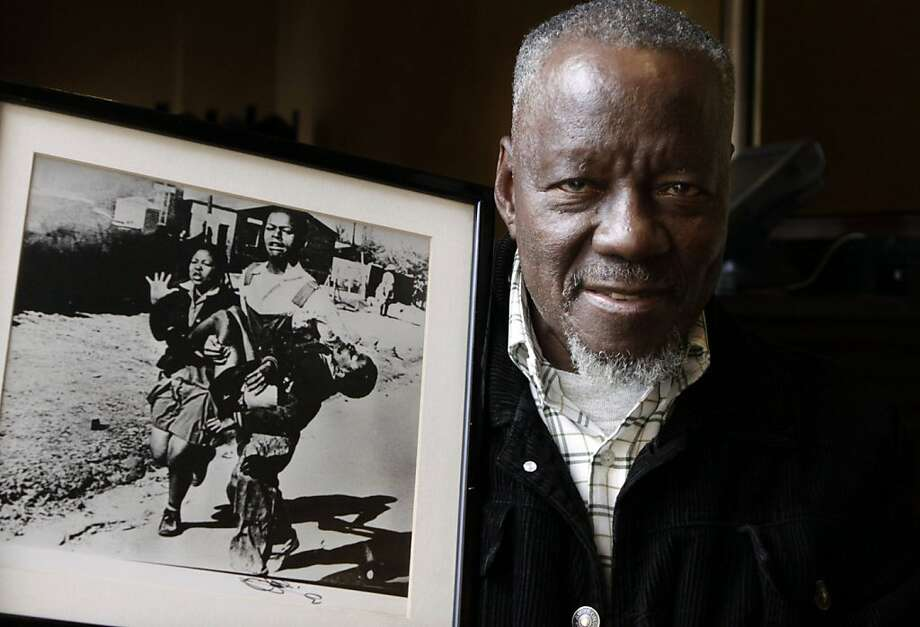 South African photographer, Sam Nzima, poses with his iconic photo showing Hector Pieterson, a 13-year-old shot by police during the 1976 Soweto uprising, in Pretoria, South Africa Wednesday, April 27, 2011. Nzima is being honored for helping expose apartheid's brutality to the world with the picture that ended his career because police were so enraged by the attention his photograph drew. (AP Photo/Denis Farrell) Photo: Denis Farrell, AP