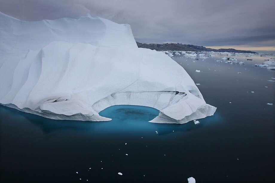 FILE - In this July 19, 2007 file photo, an iceberg is seen melting off the coast of Ammasalik, Greenland.  A new assessment of climate change in the Arctic shows the ice in the region is melting faster than previously thought and sharply raises projections of global sea level rise this century. Photo: John McConnico, AP