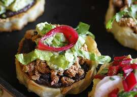 Sopes topped with black bean puree, chipotle chorizo and beet red onions, for Cinco de Mayo.