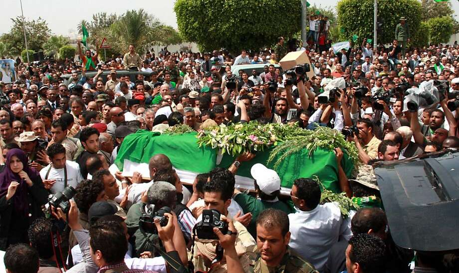 Libyan mourners carry the coffin of Seif al-Arab Kadhafi, son of embattled Libyan leader Moamer Kadhafi, during his funeral at the Al-Hani cemetery in Tripoli on May 2, 2011 after the 29-year-old was killed along with three of the leader's grandchildren in a NATO airstrike early on May 1. Photo: -, AFP/Getty Images