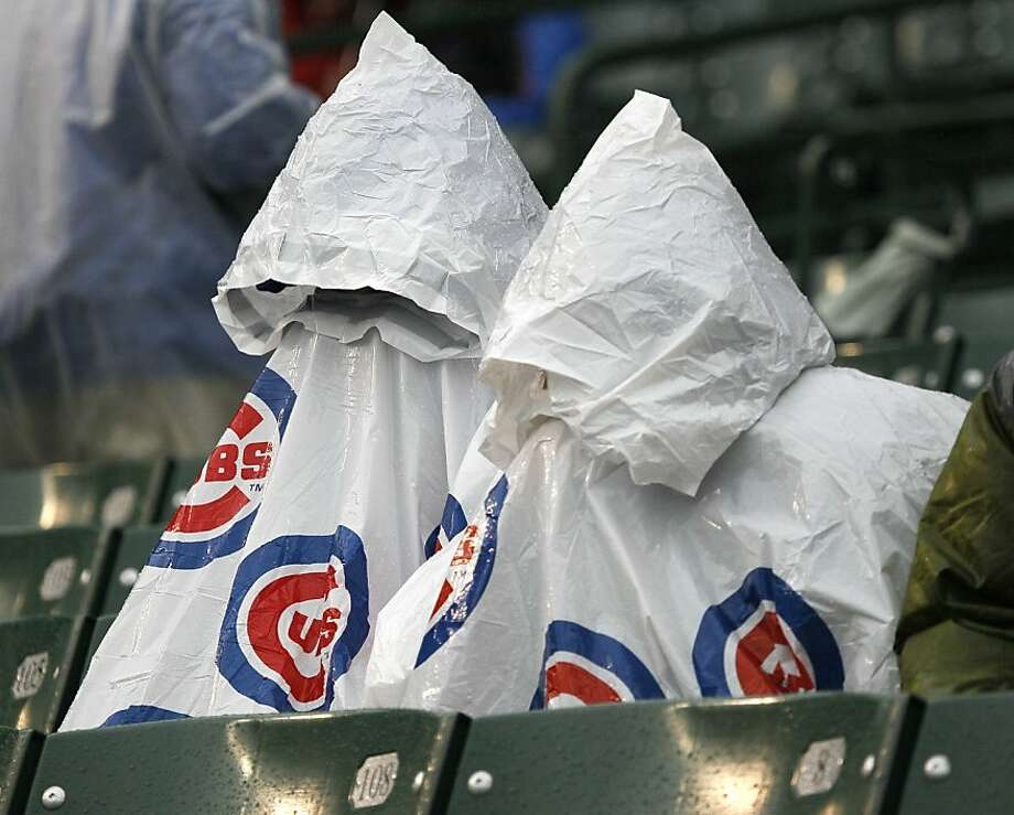 Cubs fans cover up under their Cubs ponchos during a rain delay before a baseball game between the Chicago Cubs and the Colorado Rockies, Wednesday, April 27, 2011, in Chicago. The game is postponed due to rain and scheduled for June 27. Photo: Charles Rex Arbogast, AP