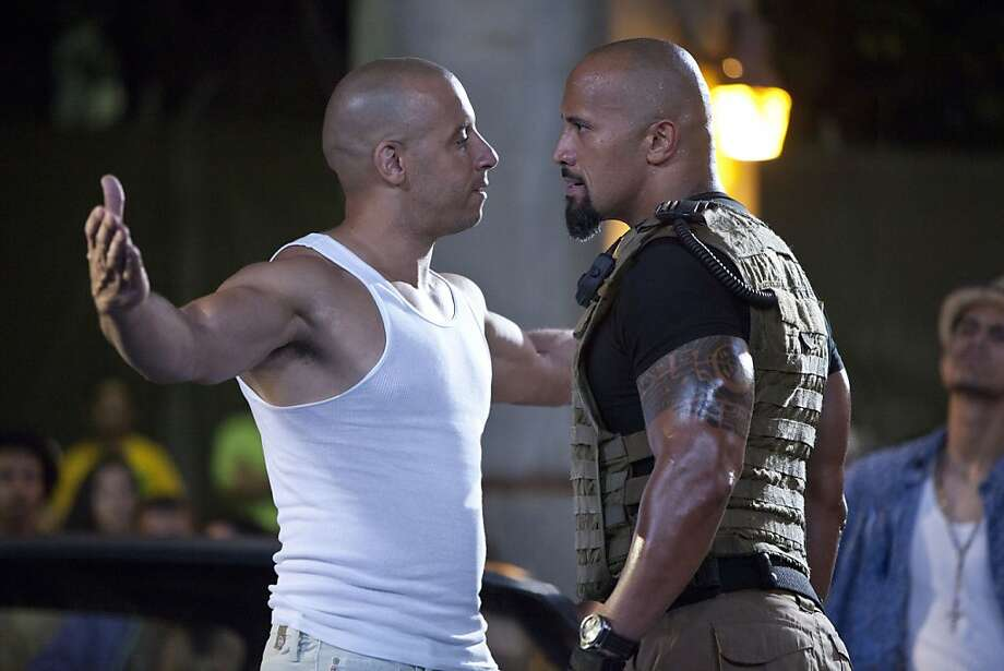 """In this film publicity image released by Universal Pictures, Vin Diesel, left, and Dwayne Johnson are shown in a scene from """"Fast Five."""" Photo: Jaimie Trueblood, AP"""