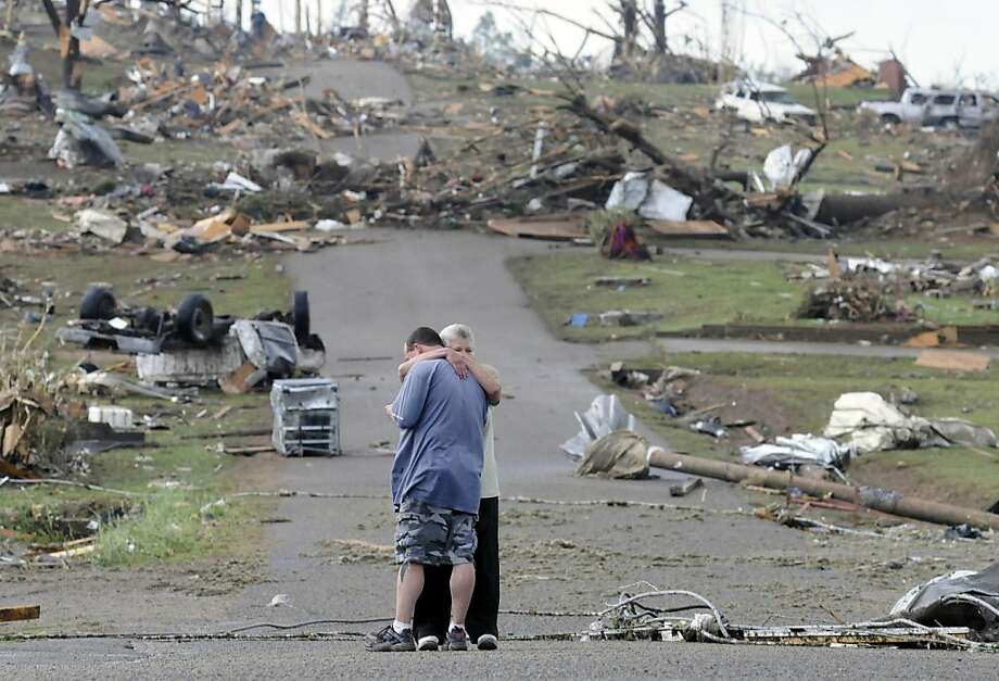 Michael Dunn is hugged by his mother Patricia Dunn as they stand in the road that lead to his house which was completely destroyed after a tornado touched down, Wednesday, April 27, 2011 in Concord, Ala. (AP Photo/Birmingham News, Jeff Roberts) MAGS OUT; NO SALES Photo: Jeff Roberts, AP