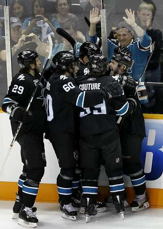 Sharks players mob Ian White (right) after his first period goal against the Detroit Red Wings in game two of the Western Conference semifinals at HP Pavilion on Sunday. Photo: Brant Ward, The Chronicle