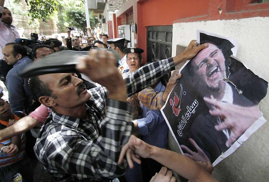 A Syrian protester beats a poster of Syrian President Bashar Assad with a shoe, as he attends protest against the on going violence in Syria, in front of the Syrian embassy in Cairo, Egypt, Tuesday, April 26, 2011.Gunfire reverberated Tuesday in the southern Syrian city of Daraa where the dead still lay unclaimed in the streets a day after a brutal government crackdown on the popular revolt against President Bashar Assad, residents said. (AP Photo/Khalil Hamra) Photo: Khalil Hamra, AP