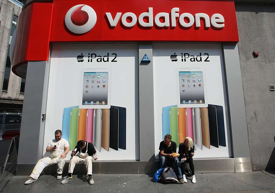 Pedestrians sit outside a Vodafone Group Plc store advertising the Apple Inc. iPad 2 for sale in London, U.K., on Thursday, April  28, 2011. Apple Inc. may face greater scrutiny in the European Union than the U.S. as regulators investigate possible data-privacy lapses betraying the location of iPhone and iPad users. Photographer: Chris Ratcliffe/Bloomberg Photo: Chris Ratcliffe, Bloomberg