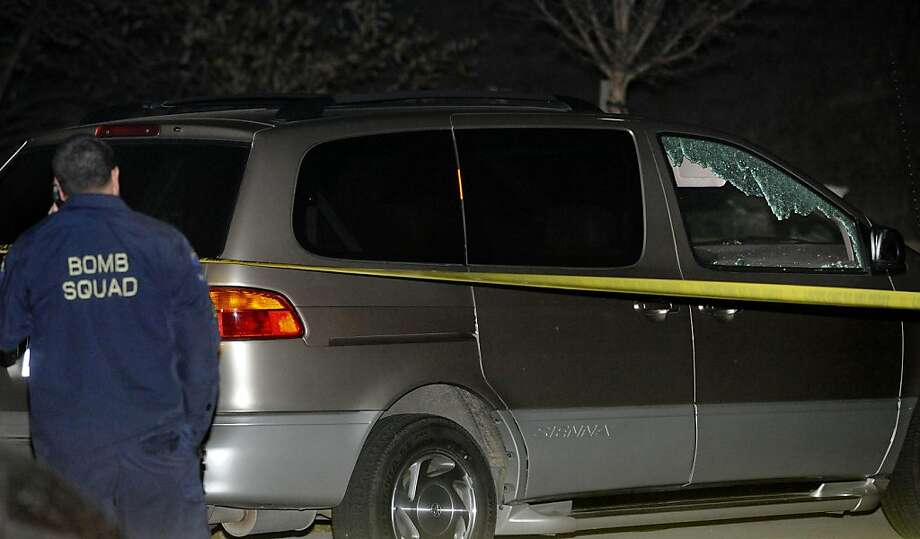 "A member of the Alameda County Bomb Squad stands next to a minivan on Springvale Drive after it was struck by a cannonball in Dublin, Calif., on Tuesday, Dec. 6, 2011. Before landing here the cannonball traveled through a home a few blocks away on Cassata Place after being misfired during the taping of an episode of the Discovery Channel show ""MythBusters"" at the Alameda County Bomb Disposal Range.  (AP Photo/Bay Area News Group, Doug Duran) Photo: Doug Duran, AP"