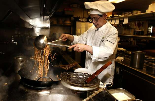 Head Chef Howard Wong, of Tommy Toy's Restaurant, in San Francisco, Ca., prepares Kia Jan Mein, braised egg noodles with chopped shrimp and chicken, on Thursday April 28, 2011. 17 North Beach restaurants and 17 Chinatown restaurants are joining together this Sunday for Noodle Fest, with the goal of boosting business for the two very different neighborhoods. Photo: Michael Macor, The Chronicle