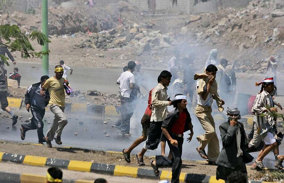 Anti-government protestors run away during clashes with Yemeni security forces, in Taiz, Yemen, Monday, April 25, 2011. Forces loyal to Yemen's embattled president attacked protesters calling for his ouster in a southern city Monday, injuring dozens, according to an opposition activist. (AP Photo/Anees Mahyoub) Photo: Anees Mahyoub, AP