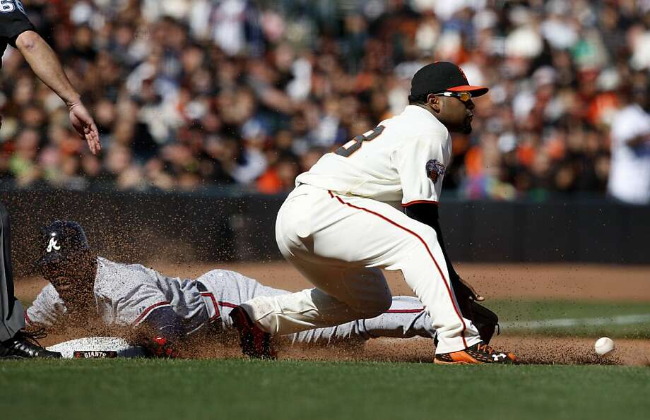 Pablo Sandoval gets a late throw in the 10th inning as Jason Heyward slides into third Sunday. Photo: Brant Ward, The Chronicle